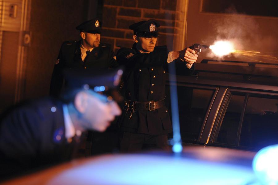 Eddy Nevens schiet richting de vluchtende gangsters (een beeld uit de reconstructie van 2010).